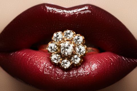 image of a diamond ring after ultrasonic cleaning, held between the lips of a woman with red lipstick.