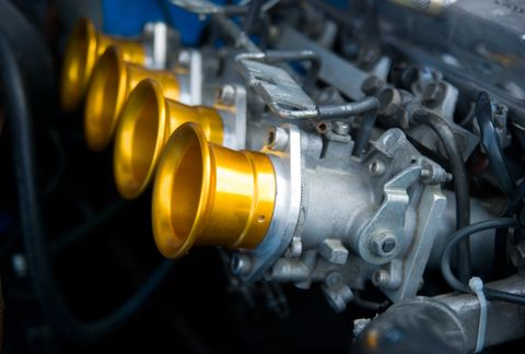 Bank of four carburetors with brightly polished brass air intakes