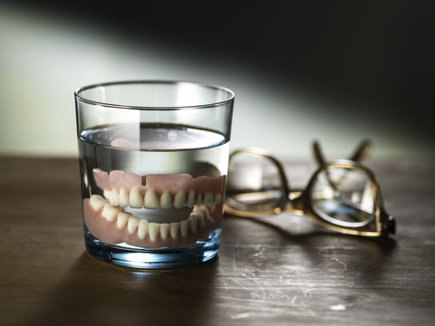 image of dentures being cleaned by soaking in a glass of water