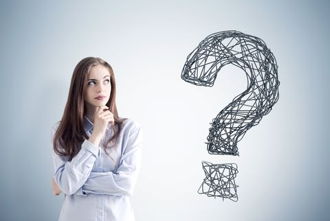 woman looking at a large question mark on the wall with a puzzled look on her face.